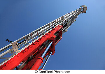 A large fire ladder - Fire truck ladder leading up into blue...