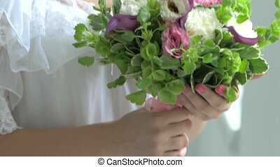 Blond girl in white dress with charming bouquet of flowers,...