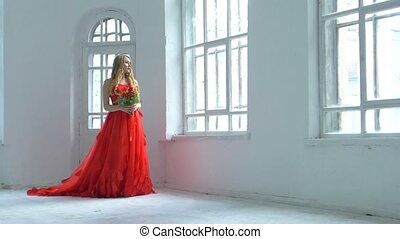 Beautiful girl in gorgeous red dress walking past the...