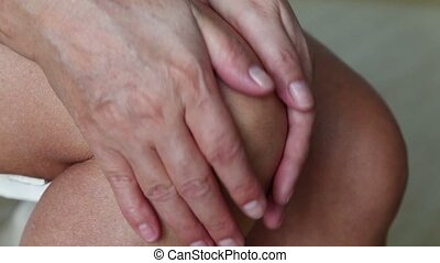 Woman With Knee Pain Close Up - Knee pain, woman rubbing her...