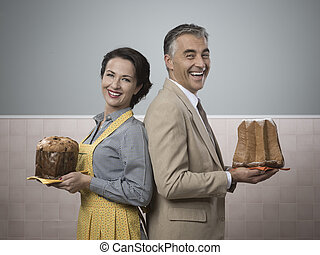 Smiling couple at home with christmas cakes - Smiling...
