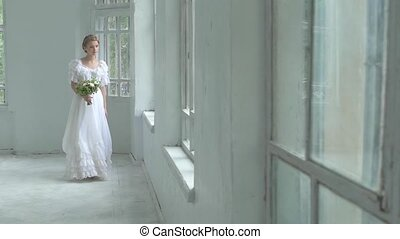 Beautiful girl in white dress walking past the window with flowers, slow motion