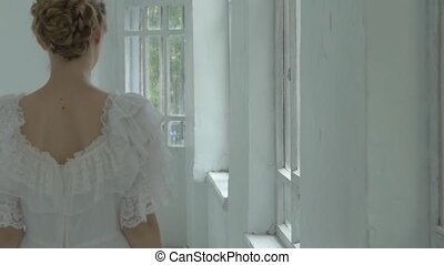 Beautiful girl in white dress walking past the window with...