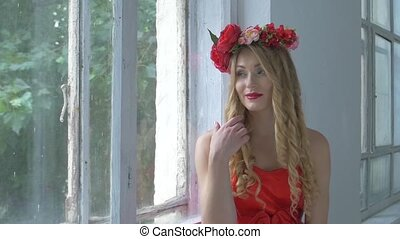 Pretty young woman with wreath of red flowers on her head...