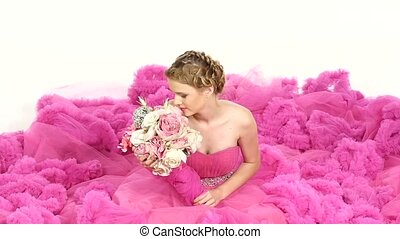 Pretty young woman in gorgeous pink dress, sitting, smells the flowers, smiling, on white, slow motion