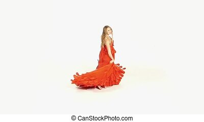 Beautiful girl in gorgeous red dress whirling, isolated on...