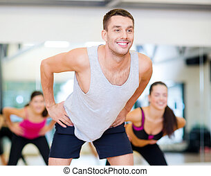 smiling male trainer working out in the gym - fitness,...