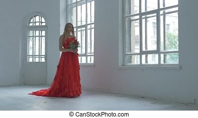 Pretty girl in gorgeous red dress walking past the vintage windows with flowers, slow motion