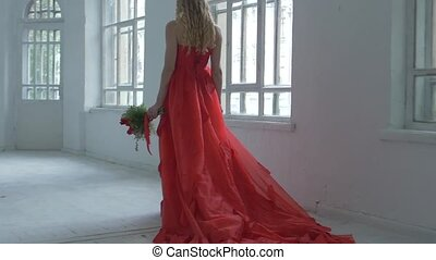 Pretty girl in gorgeous red dress walking past the vintage windows with flowers and waves her hair, slow motion