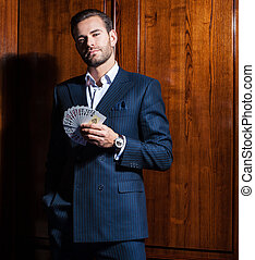 Handsome man in suit poses with cards on wooden background -...