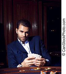 Handsome guy plays cards in casino - Handsome guy in blue...
