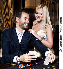 Beautiful couple play cards in casino - Beautiful couple...