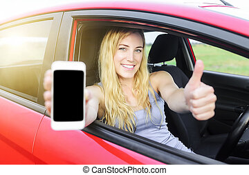 Driver woman showing her smartphone. - Happy blonde woman...