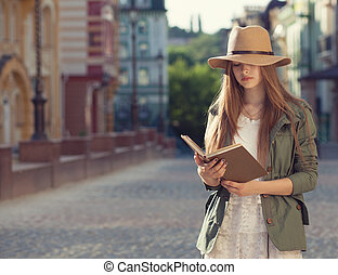Yuccie girl reading book outdoors