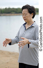 Asian Senior Practice Taichi, Qi Gong exercise next to the...