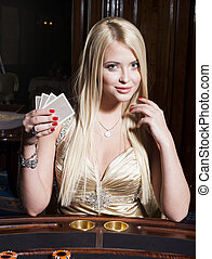 Beautiful blonde woman in elegant dress plays poker