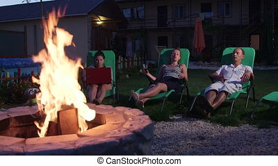 Friends having outdoor garden party with drinks relaxing near fire pit