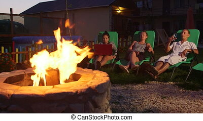 People relaxing in back yard sitting on patio loungers near...