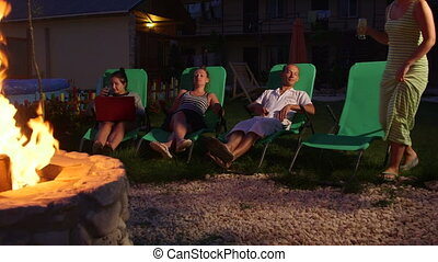 Friends relaxing on grassy lawn in backyard with drinks near stone fire pit