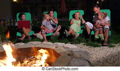 Family sitting on patio loungers in backyard near flaming...