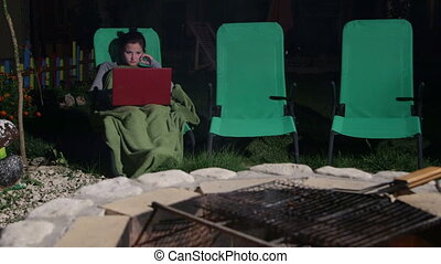 girl wrapped by rug sitting on lounger in backyard with laptop near fire pit