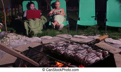 Grilling barbecue on stone fire pit in backyard family...