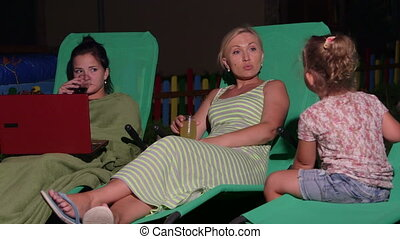 Mother with two daughters sitting on patio loungers in back...