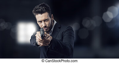 Cool handsome man pointing a gun - Cool aggressive man in...