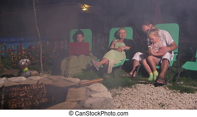 Family sitting on patio loungers grilling barbecue on stone fire pit in backyard