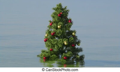 Decorated Christmas Tree in the turquoise water on a tropical beach