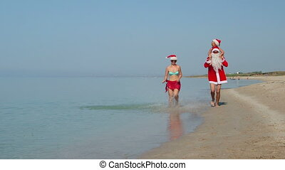 Family enjoying Christmas beach getaway running along surf...