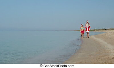 Family in Christmas costumes walking along sand beach