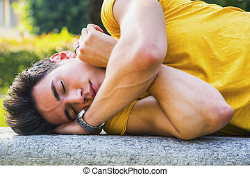 Attractive young man sleeping on stone bench outdoor in city...
