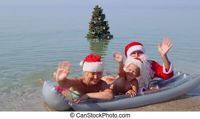 Family enjoying tropical beach holiday near Christmas tree in surf greeting