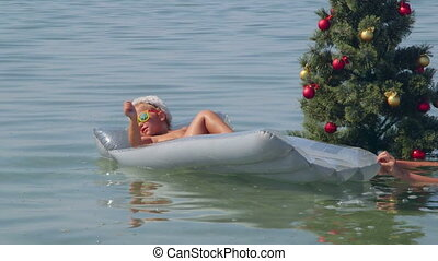 Funny little girl near Christmas tree in water on sand beach...