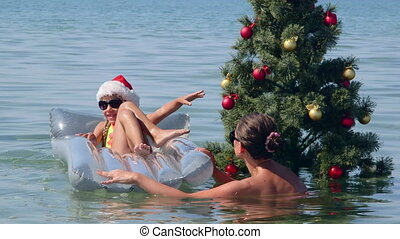 Family tropical beach vacation near decorated Christmas tree in water