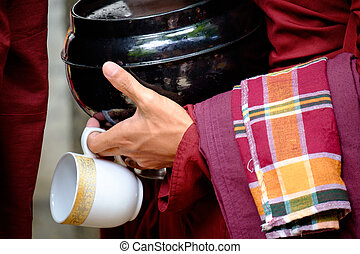 Colorful details of buddhist monk hands holding a bowl and...