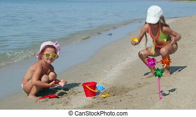 Cute kids have fun playing with beach sand toys during...