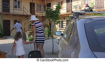 Family traveling by car arrived to spend summer vacation in small tourist hotel
