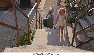 Family with luggage on summer holidays arrived in small tourist hotel