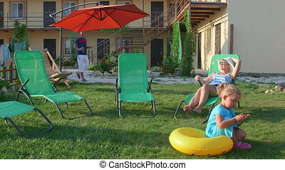 Family relaxing on patio loungers on grass lawn of small...