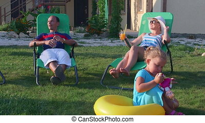 Family with drinks relaxing in sun loungers on grass lawn of...