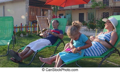 Family on summer vacation resting on grass lawn of small...