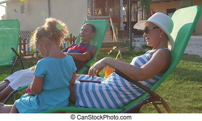 Family with drinks sitting in sun loungers on grass lawn of...
