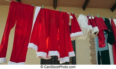 Santa Clause costume hanging on clothesline in the back yard