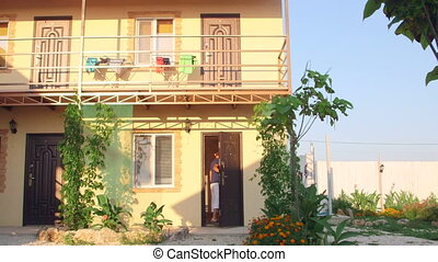 Small cheap resort hotel exterior in summer pan shot