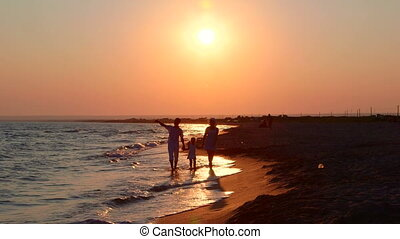 Family summer beach vacation at sunset mother father and kid...