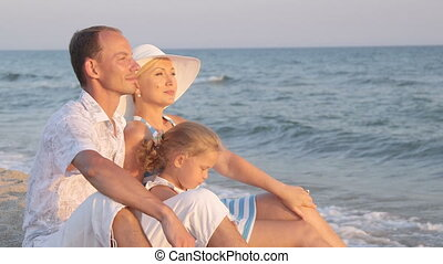 Young family with her daughter sitting in the evening on the beach looking away