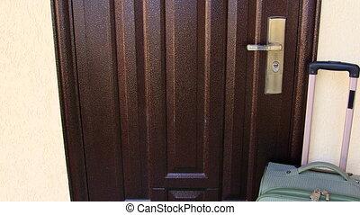 Welcome home door mat with suitcase travel background tilt...