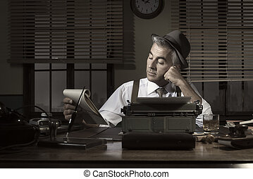 Professional reporter working late at night at his desk with...